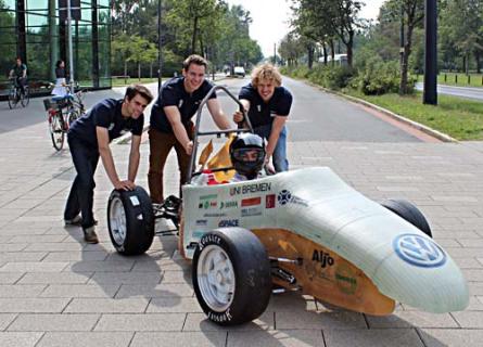"""Umweltschonend, aber schnell: Max, Lambert und Sebastian vom """"Bremergy Racing""""-Team mit ihrem eigens konstruierten Rennwagen, dem """"BreMo13"""". Im September wird Fahrer Stas in Italien bei der Formula Student Electric damit an den Start gehen."""