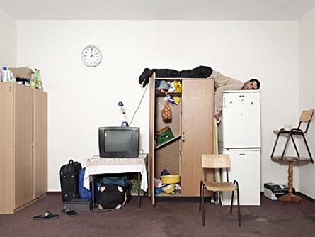 """Die Fotoserie """"Ali"""" zeigt in tragikomischen Portraits die Verzerrtheit und Fremdbestimmung Asylsuchender in Deutschland. Die abgebildeten Menschen wirken deplatziert, isoliert und machtlos – ein Sinnbild für den Zustand des Vorübergehenden, in dem sich die Geduldeten befinden."""