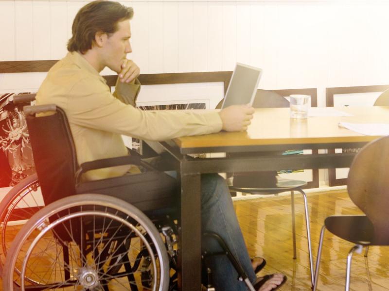 Das Bild zegt einen Mann im Rollstuhl, der an einem Tisch sitzt und sich am PC über eine Berufsunfähigkeitsversicherung informiert.