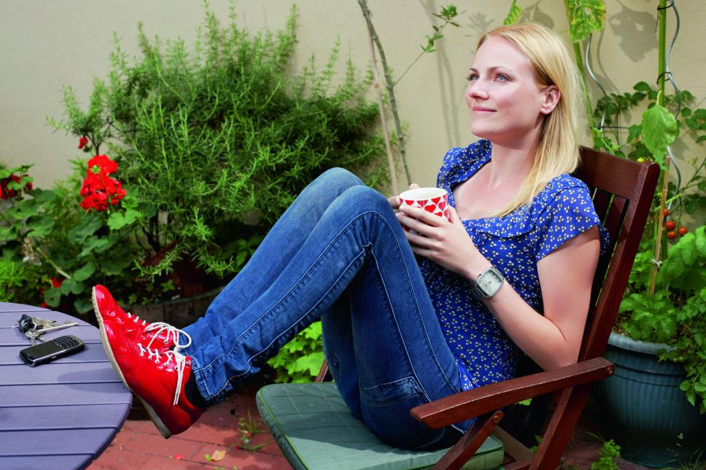 Junge Frau sitzt auf einem Gartenstuhl und entspannt.